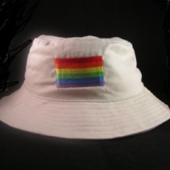This stone colored brushed cotton twill bucket hat has an embroidered rainbow flag emblem. Perfect to crush in your pocket for that sunny day.