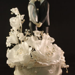 This Mature Gay Men Wedding Cake Topper features a white cascading sprig of velvet roses accented with faux pearls and crystals and a string of crystals around its porcelain base. The gray haired couple truly celebrates the emotion of found joy as they lovingly embrace each other.