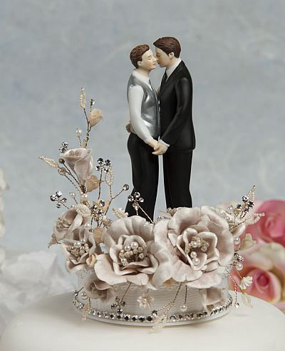 This gay men wedding cake topper features a white cascading sprig of velvet roses accented with faux pearls and crystals and a string of crystals around its porcelain base. The couple truly celebrates romance as they lovingly embrace each other
