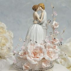 This lesbian wedding cake topper features a white cascading sprig of velvet roses accented with faux pearls and crystals and a string of crystals around its porcelain base. The couple truly celebrates romance as they lovingly embrace each other. Hand painted with attention to every detail